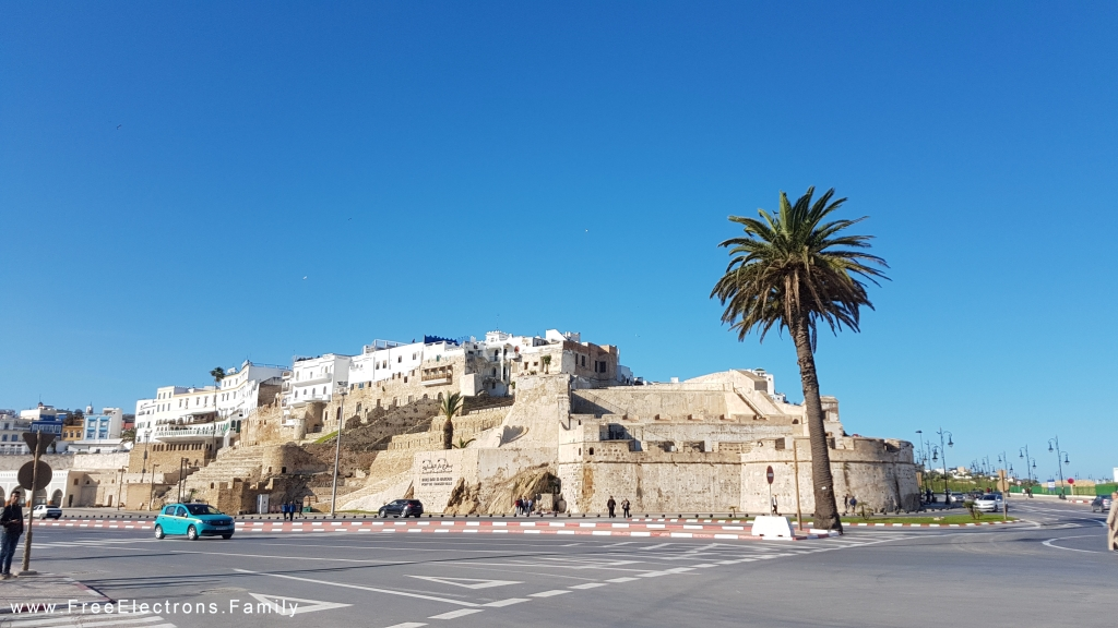A near-empty wide intersection in front of an ancient wall fortification .
