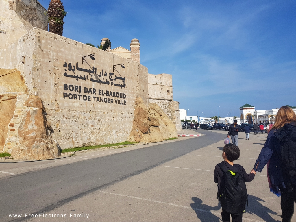 """A young boy, holding his mother's hand, looks at an ancient wall with modern writing in Arabic, French and Berber that reads """"Port de Tanger Ville""""."""