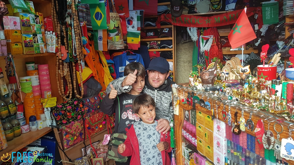 Two young boys and a shop owner of a souvenir shop smile and give a thumbs up for the camera.
