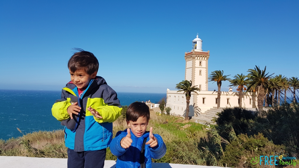 Two young boys posing for the camera; a lighthouse overlooking the ocean in the background.