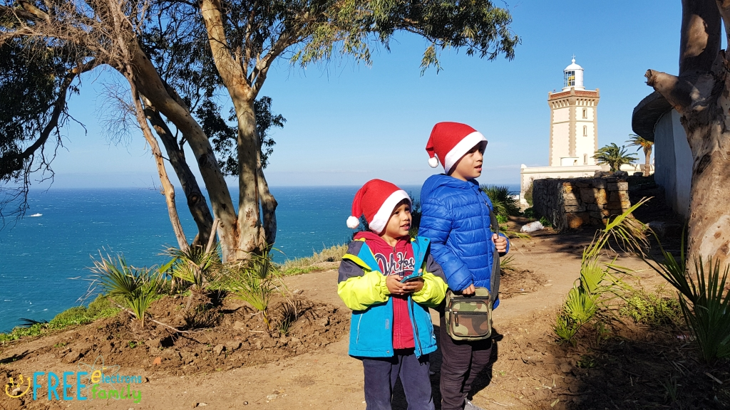 Two young boys wearing Santa Claus hats in the woods with a lighthouse and the ocean in the background.