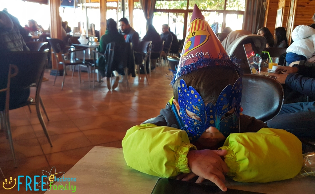 A young boy with a carnival mask and a FC Barcelona hat sits in a restaurant.